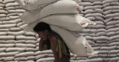 A worker carries sacks of rice