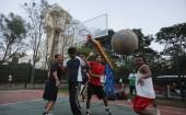 Employees of IT companies play on a basketball court after work at the Electronics City IT district in Bangalore.