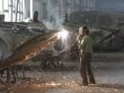 A worker welds at a machinery manufacturing factory