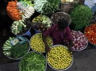 A vendor arranges vegetables