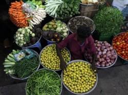 A vendor arranges vegetables