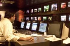A news producer sits inside a news studio