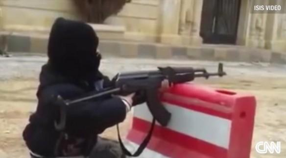 A 10 year old boy fires an AK 47 in an ISIS training camp.