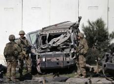 The US troops keep watch near a damaged vehicle at the site of suicide attack in Kabul September 16, 2014.