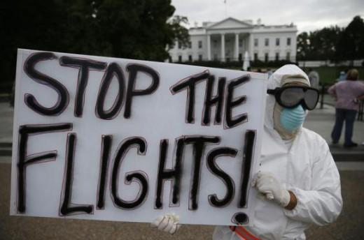 Protestor Jeff Hulbert of Annapolis, Maryland holds a sign reading ''Stop the Flights'' as he demonstrates in favor of a travel ban to stop the spread of the Ebola virus, in front of the White House in Washington.