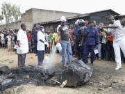 A man extinguishes the burnt remains of a man who was lynched by a mob, as policemen take photographs, in Beni, in the Democratic Republic of Congo's North Kivu province, October 31, 2014.