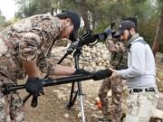 Rebel fighters prepare to fire a machine gun towards forces loyal to Syria's President Bashar al-Assad in the Jabal al-Akrad area in Syria's northwestern Latakia province November 25, 2014
