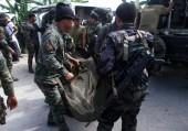 Philippine National Police (PNP) carry a body bag, containing a member of the Special Action Force, to a van in Mamasapano town, Maguindanao province, January 26, 2015. At least 30 people were killed in heavy fighting between police and Muslim rebels in t