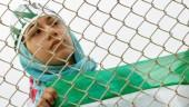 An Iranian woman watches the practice session of Iran's national soccer team from behind a fence because women are banned from entering the stadium at Azadi (Freedom) sports complex in Tehran, Iran, May 21, 2006.