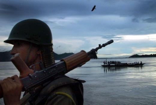 An Indian paramilitary trooper stands guard on the banks of the river Brahmaputra