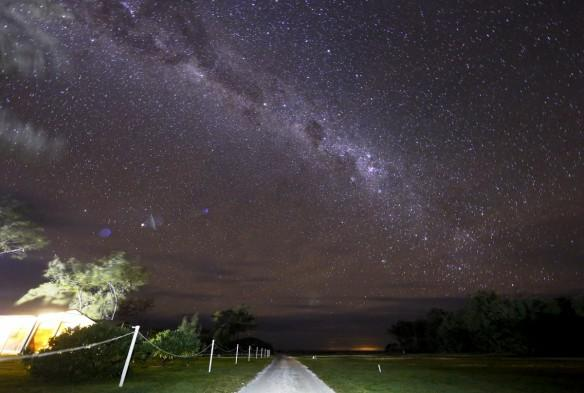 The Milky Way can be seen in the sky above a path and huts on Lady Elliot Island