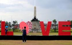 """People take pictures of a """"LOVE"""" display day before Valentine's Day in Rizal park"""