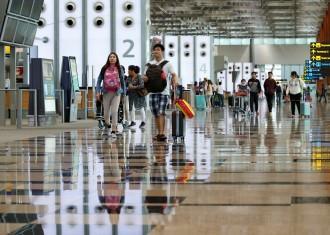 Passengers walk in Singapore's Changi Airport Terminal 3