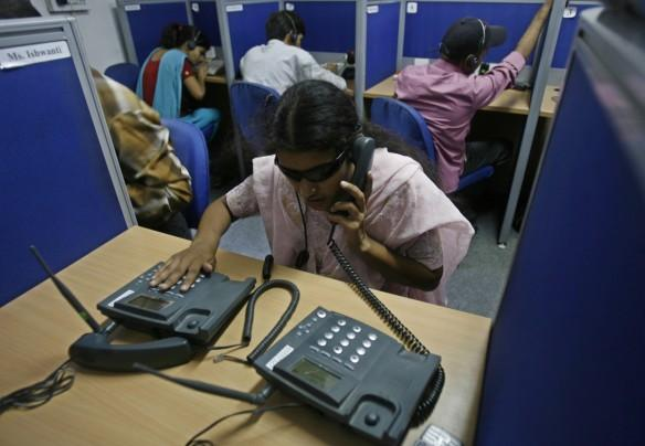 A visually impaired trainee tends to a phone call at a training call centre for the visually challenged in New Delhi October 8, 2009.