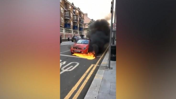 Bystanders attempt to stop a burning car rolling along a busy London street