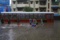 People wade through a water-logged road past a stalled passenger bus during rains in Mumbai, August 29, 2017.
