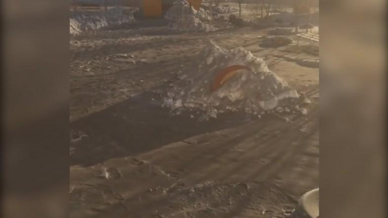 Black snow covers a playground in Kazakhstan