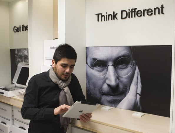 Man checks Apple iPad as he stands next to portrait of late Apple co-founder Jobs at shop in Payetakht computer centre in northern Tehran