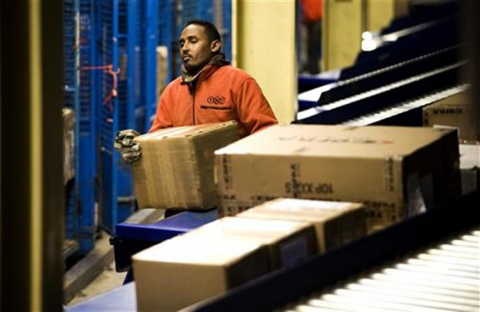 (Representative Picture) A worker loads parcels ready for transport at the global express company TNT's road hub in Duiven. (Credit: Reuters)