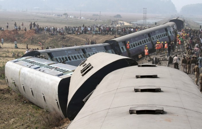 Onlookers and rescue workers gather around the derailed coaches of a passenger train in Bangapara village in February
