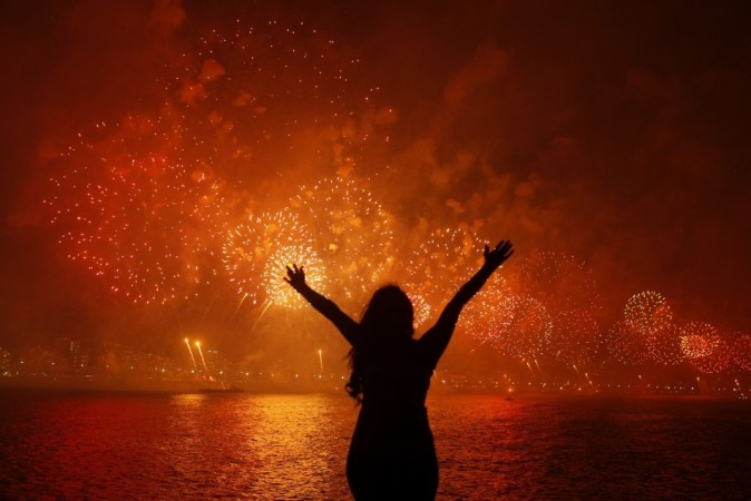 A woman celebrates the New Year as she watches fireworks exploding above Copacabana beach in Rio de Janeiro