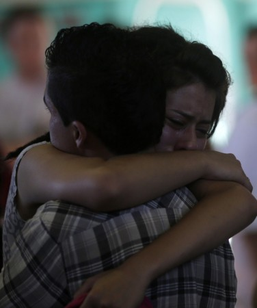 Relatives of victims of the fire at Boate Kiss nightclub react during a collective wake in Santa Maria