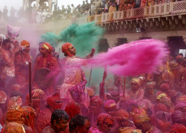 "People throw coloured powder as they celebrate ""Lathmar Holi"" at Nandgaon village in the northern Indian state of Uttar Pradesh, March 22, 2013. In a Holi tradition unique to Nandgaon and Barsana villages, men sing provocative songs to gain the"
