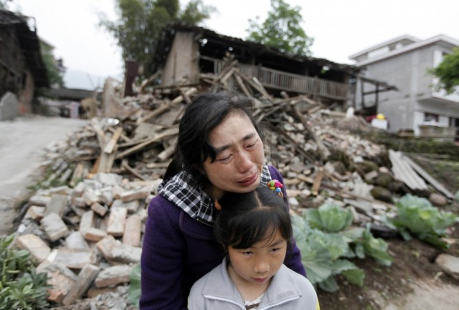 Song Zhengqiong, holding her daughter, cries in front of her damaged house after a strong 6.6 magnitude earthquake at Longmen village, Lushan county in Ya'an, Sichuan province April 21, 2013.(Reuters)