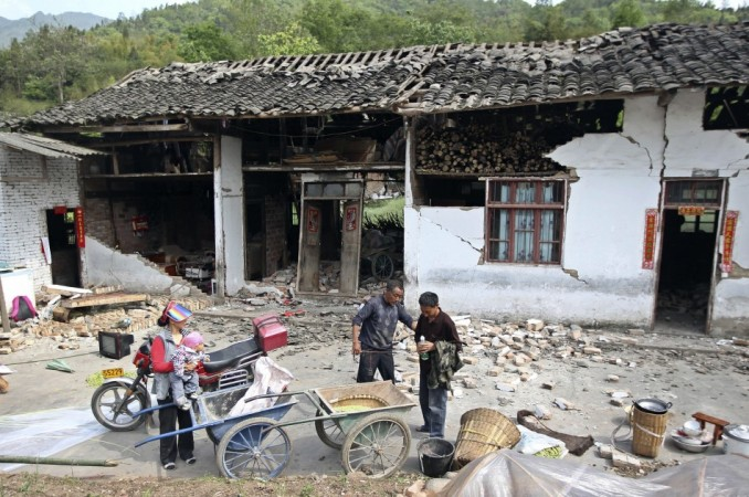 People stand outside a damaged house after a strong 6.6 magnitude earthquake hit, at Longmen village, Lushan county, Ya'an, Sichuan province April 20, 2013. (Reuters)