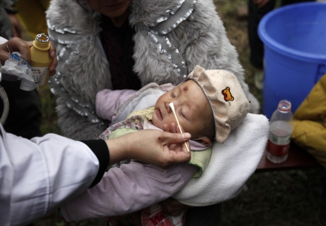 A three-month-old baby, whose mother was killed in a strong 6.6 magnitude earthquake, receives treatment at a medical point in Lushan county of Ya'an, Sichuan province April 21, 2013. (Reuters)