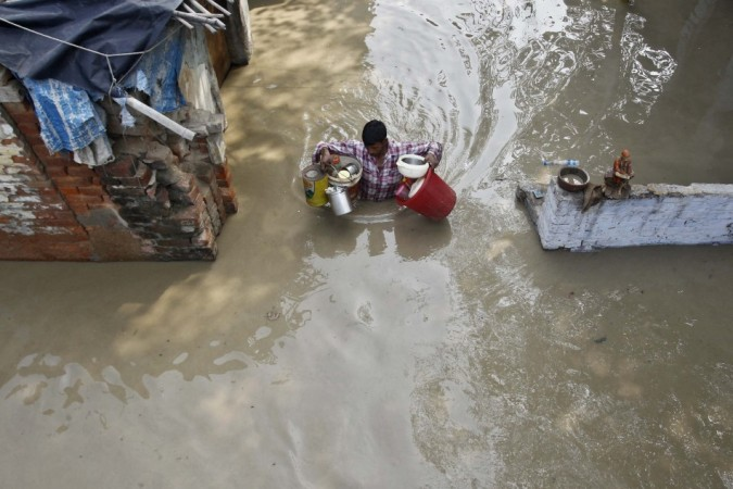 A resident carries his belongings through an alley flooded with the rising water level of river Yamuna after heavy monsoon rains in New Delhi (Reuters)