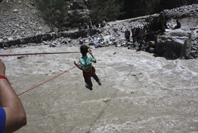 Indian Army personnel rescue a stranded child with the help of ropes through the flooded waters of a river in the Himalayan state of Uttarakhand(Reuters)