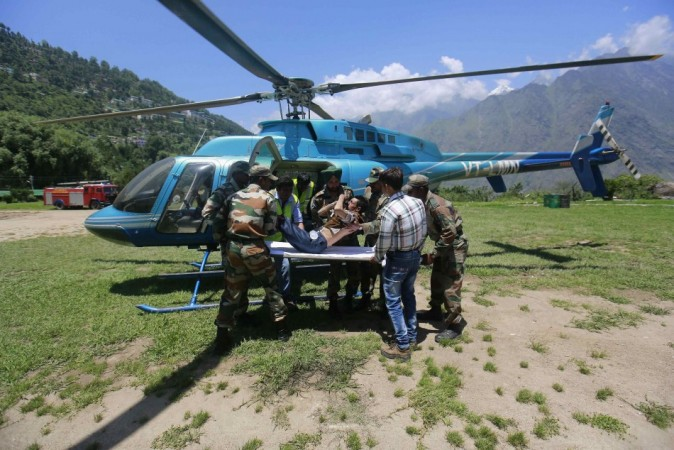 An injured pilgrim is put on a stretcher next to a helicopter by soldiers and volunteers during a rescue operation at Joshimath, in the Himalayan state of Uttarakhand (Reuters)