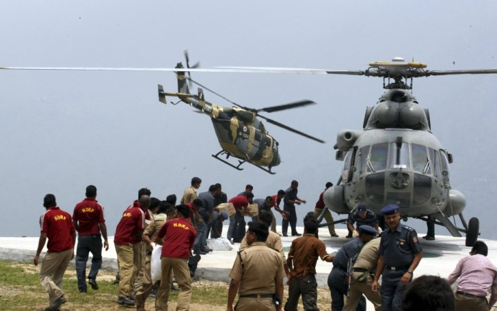 Handout of personnel from the Indian armed forces carrying relief supplies from a helicopter for stranded people at Guptkashi after heavy rains in the Himalayan state of Uttarakhand (Reuters)