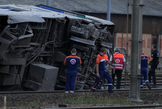 Rescue workers stand next to the wreckage of a derailed intercity train at the Bretigny-sur-Orge station near Paris(Reuters)