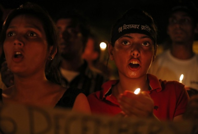Demonstrators shout slogans as they hold candles during a candle light vigil