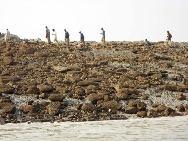People walk on an island that rose from the sea following an earthquake, off Pakistan's Gwadar coastline in the Arabian Sea.