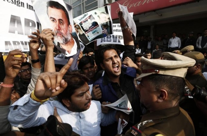 Activists of the Akhil Bharatiya Vidyarthi Parishad (ABVP), linked to India's main opposition Bharatiya Janata Party (BJP), holding posters of Tarun Tejpal, editor-in-chief of India's leading investigative magazine, shout slogans as police try t