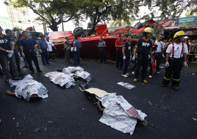 Bodies of passengers lie beside a bus after it fell off an elevated expressway and crashed into a van below in Taguig city, south of Manila December 16, 2013. At least 21 people were killed during the incident, according to the police.