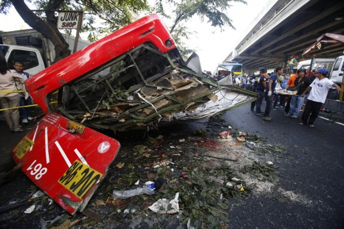 Rescuers carry a body on a stretcher as they walk past a bus after it fell off an elevated expressway and crashed into a van below in Taguig city, south of Manila December 16, 2013.