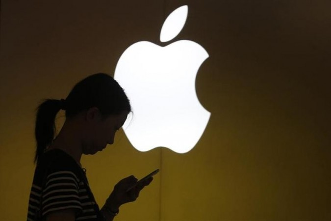 A woman looks at the screen of her mobile phone in front of an Apple logo outside its store in Shanghai.