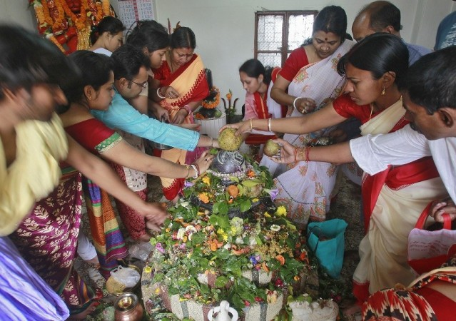 Hindu devotees place their offerings on a Shivling (a symbol of Lord Shiva) while praying inside a temple on the occasion of the Mahashivratri festival in Agartala, capital of India's northeastern state of Tripura