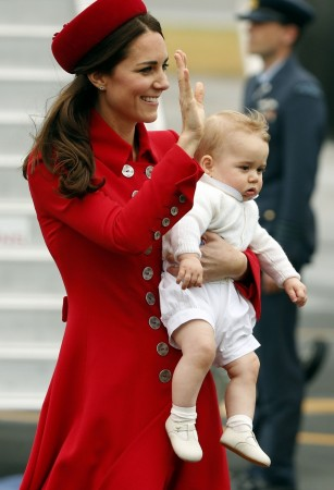 Catherine, the Duchess of Cambridge, holds her son Prince George after disembarking their plane with her husband Britain's Prince William after arriving in Wellington