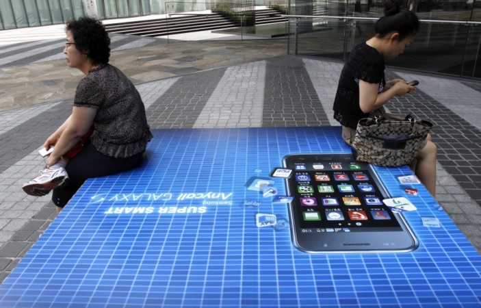 File picture shows people holding their mobile phones as they sit on an advertisement of Samsung Electronics' Galaxy S smartphone in Seoul