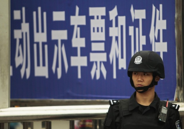 A policeman stands guard at a railway station after a knife attack in Guangzhou, Guangdong province May 6, 2014. REUTERS/Alex Lee