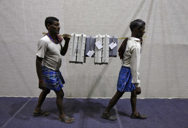 Labourers carry EVMs at an election material distribution centre on the eve of the final phase of general election in Kolkata