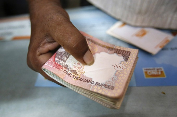 A customer hands a bundle of Indian Rupee currency notes to a teller at a financial institution in Mumbai