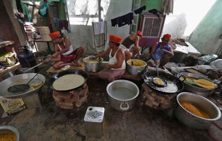 Sweets makers wearing caps of India's main opposition BJP prepare