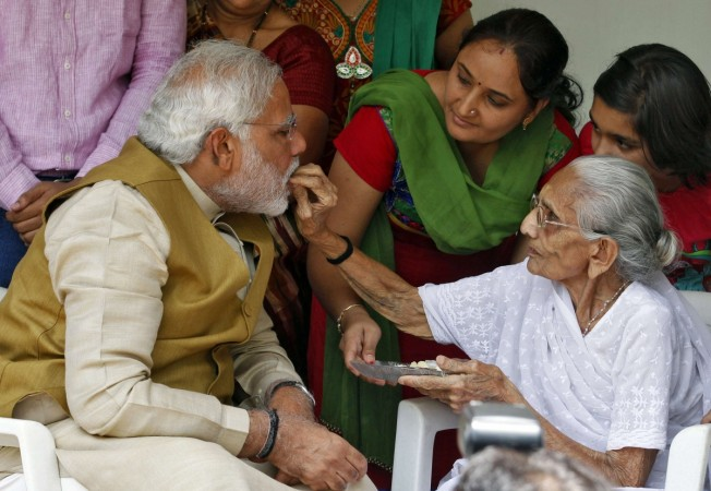 Hindu nationalist Modi, the prime ministerial candidate for India's BJP, talks with his mother Heeraben at her residence in Gandhinagar