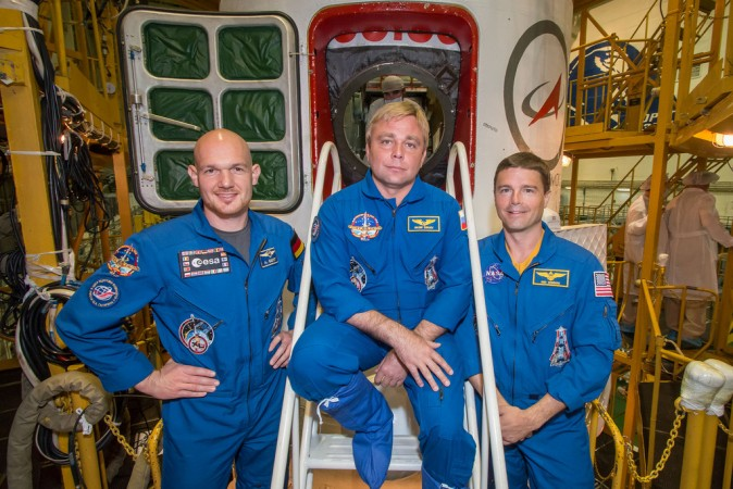 At the Baikonur Cosmodrome in Kazakhstan, Expedition 40 Flight Engineers Alexander Gerst (left), Maxim Suraev (center) and Reid Wiseman pose for pictures in front of their Soyuz TMA-13M spacecraft. (NASA/Victor Zelentsov)
